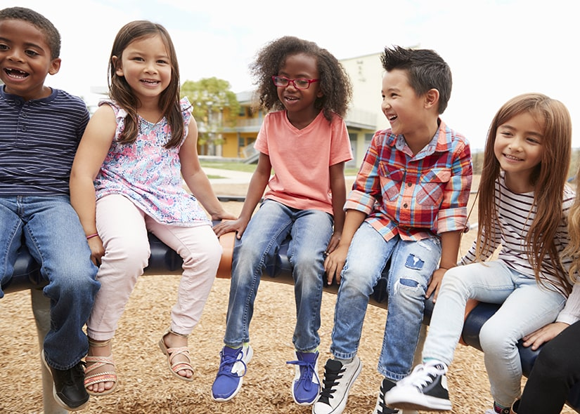 Kids hanging around a playground during recess.